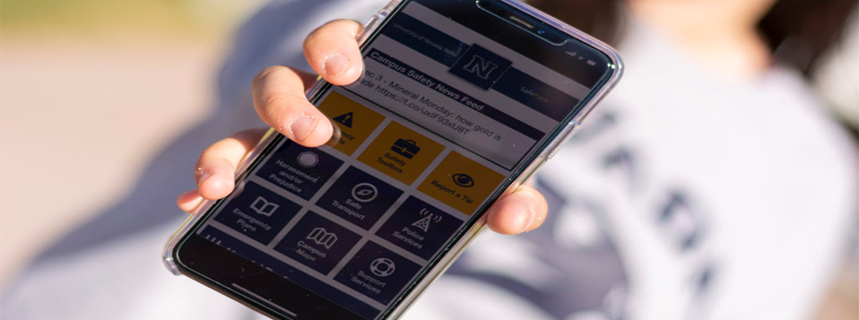 Student holding their phone with the Nevada SafePack app open